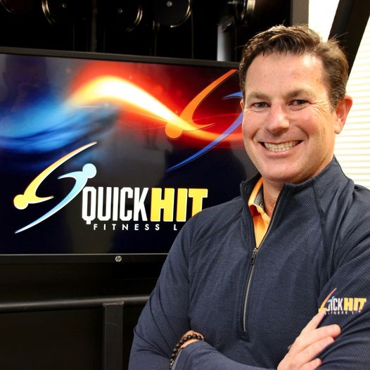 Patrick Ilfrey poses for a photo in front of QuickHIT's patented machine.